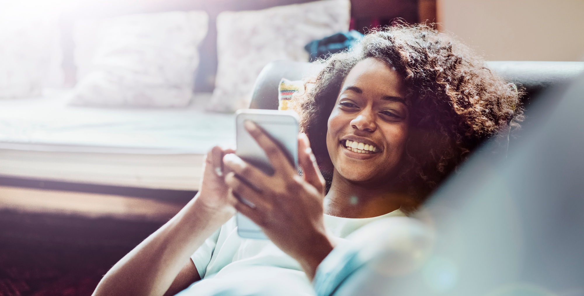 woman-laying-on-couch-smartphone-smiling.jpg